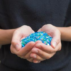 Mani che raccolgono flakes di plastica